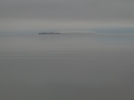 The FOG! The fog engulfs a tiny island out in the bay.